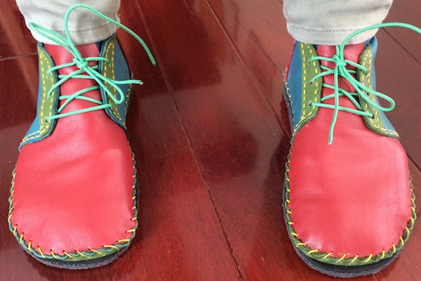 A pair of red, blue and green ankle boots with yellow stitching and green laces
