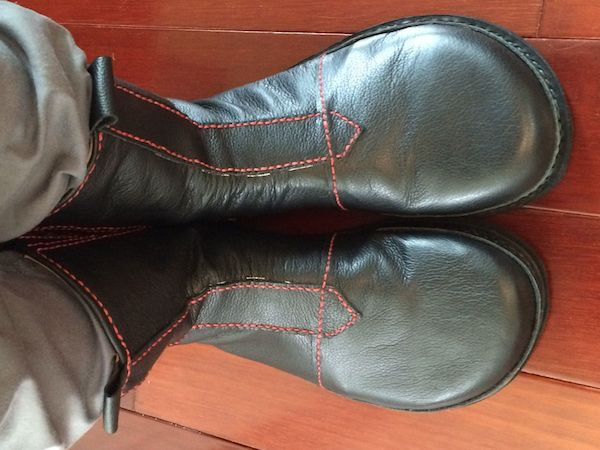 Black leather calf-high boots with red stitching.