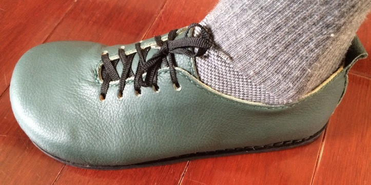Green sneaker-like shoe with black sole and laces