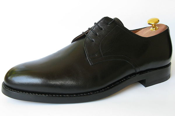 A black leather man's derby shoe with a shoe tree in it