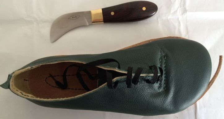 A curve-bladed knife next to a shoe with a piece of thick sole leather protruding