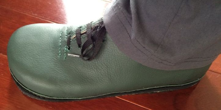 A green Oxford shoe with grey trousers