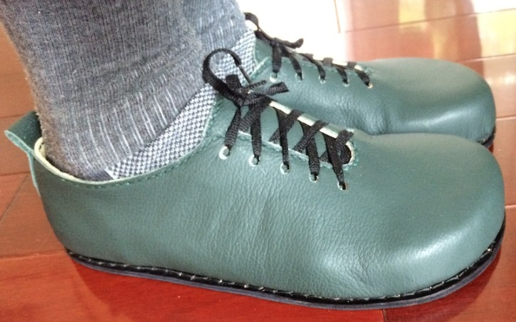 A pair of handmade green laced shoes with rounded toes