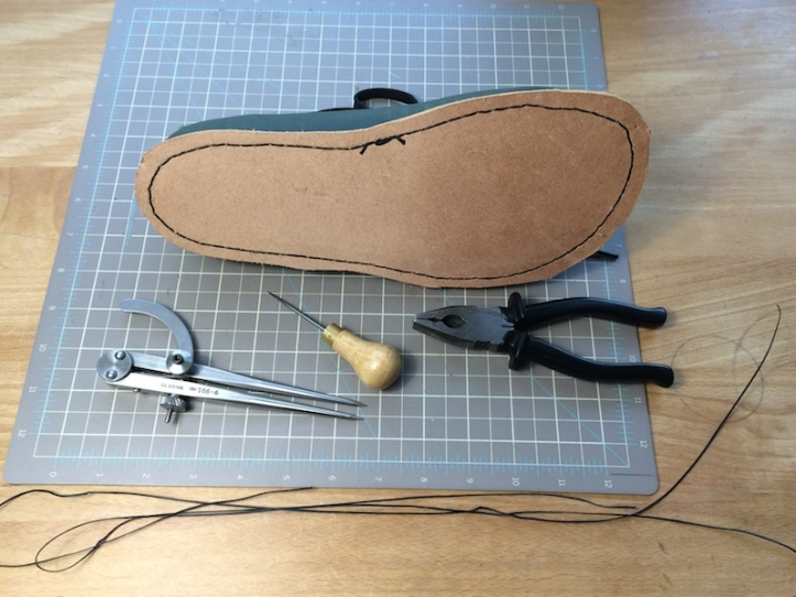 Calipers, awl, pliers, thread and nearly finished shoe