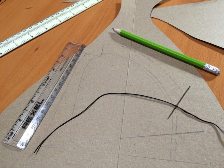 A length of black thread with a needle through it, two plastic rulers and a green pencil lying on a piece of card