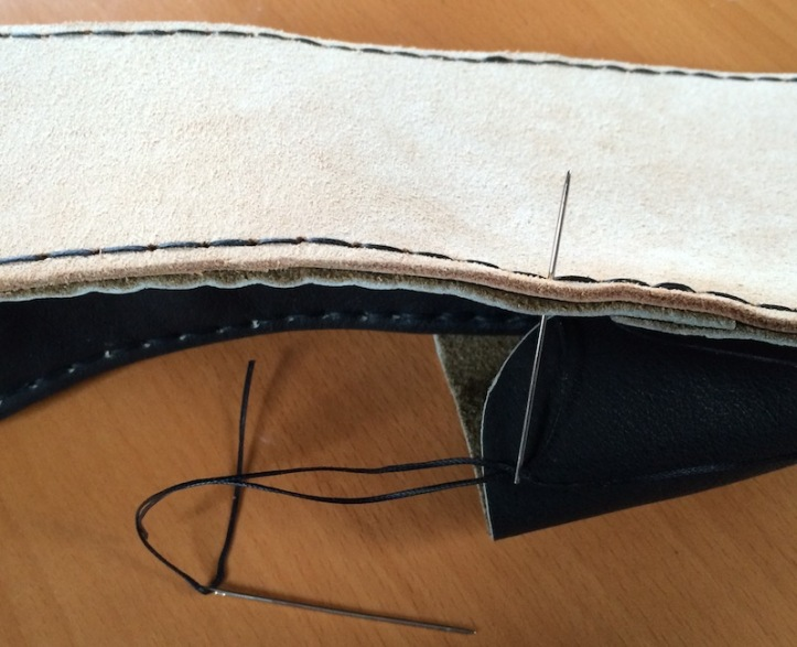 A needle piercing the leather of sole and upper