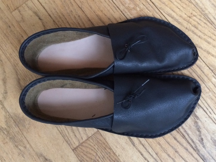 A pair of dark brown soft shoes with light brown soles