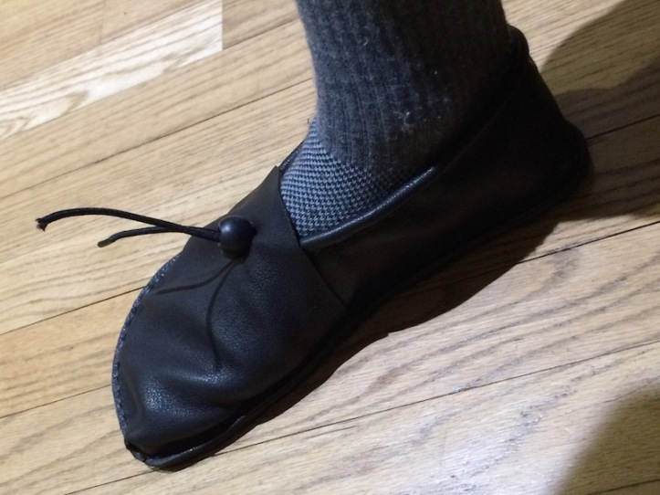 A brown leather shoe with a black lace and grey sock