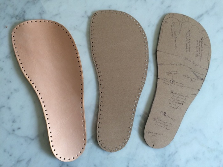 A tan leather sole plus two foot-shaped cardboard pattersn