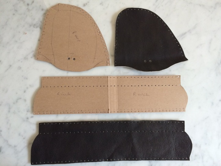 Tan card and brown leather pieces with stitching holes punched.