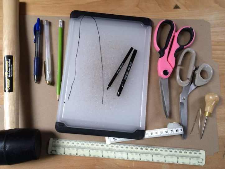 Scissors, mallet, measuring tapes and other tools set out on a piece of card