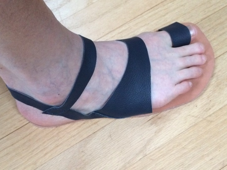 A foot wearing a minimalist brown leather sandal