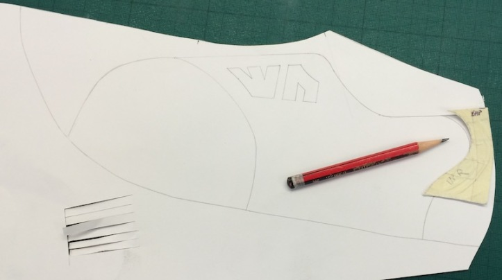 Using a pencil to trace around a masking-taped piece of pattern