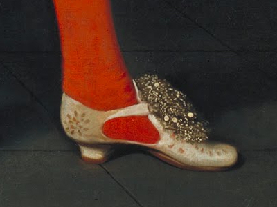A red-stockinged foot in an ornate, heeled cream and gold shoe