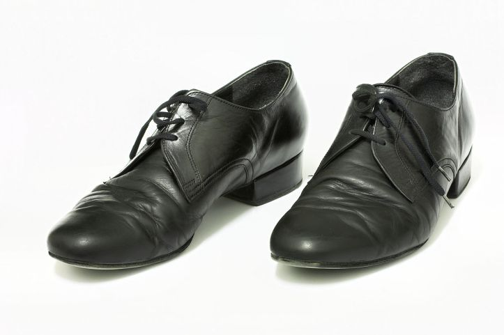 Black men's dress shoes photographed against a white background