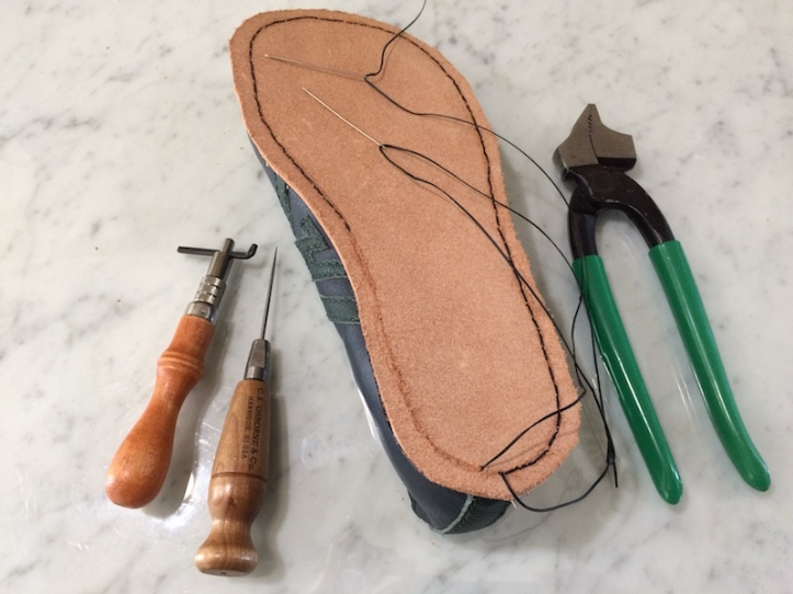 A partly hand-stitched outsole, together with pliers, needles, awl and grooving tool