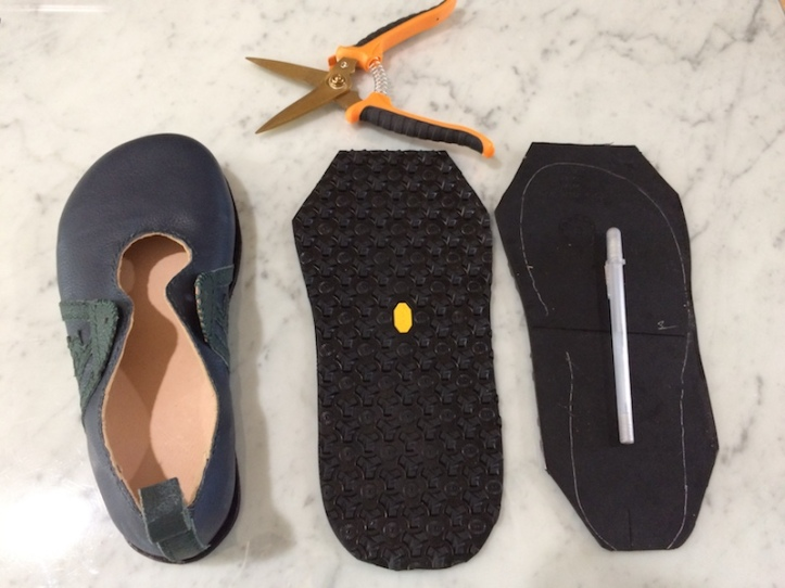 Two pieces of Vibram soling material, a pair of shears used to cut them, a silver pen for marking the outsole outline, and one of the shoes they'll be glued to