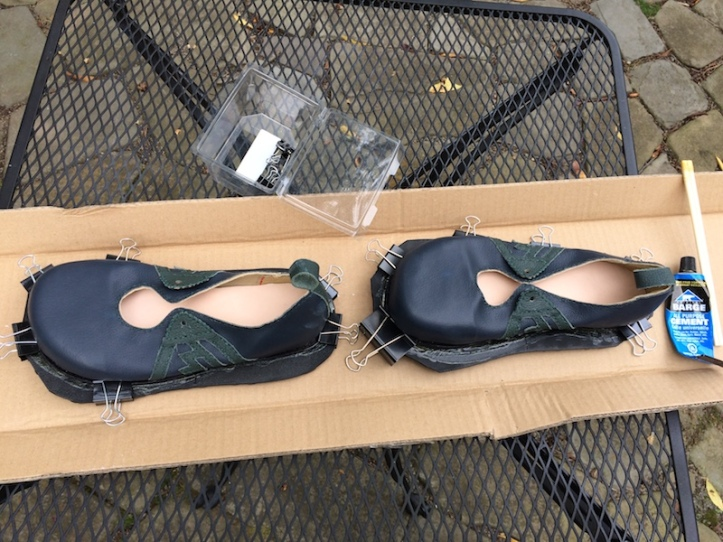 Two shoes clamped to rubber soles, bulldog clips around the perimeter
