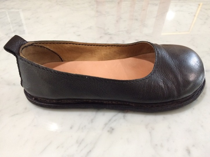 A black leather flat ladies' shoe with scalloped, low front