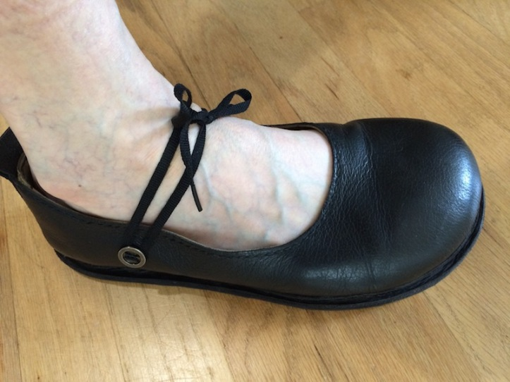 A flat black court shoe with a flat black nylon shoelace attachement.