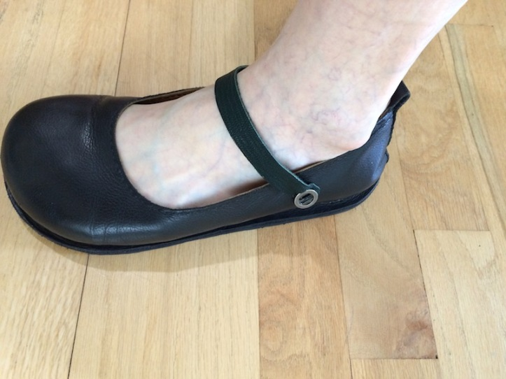 A dark green strip of goatskin attached over the foot, securing the black shoe seen in other photos.