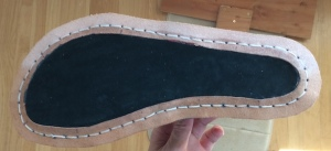 A dark green piece of leather filling the space inside an unbroken welt on the sole of a lasted shoe.