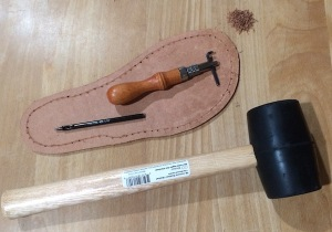 Rubber mallet, grooving tool and 00 punch lying near a prepared outsole