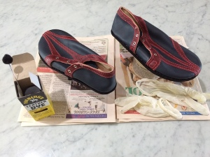 Two shoes on a piece of newspaper together with a pot of dye, a dye applicator, and a pair of latex gloves