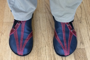 A pair of blue leather shoes with red highlights, at the end of fawn-trousered legs